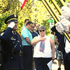 SHEILA SELMAN | THE GOSHEN NEWS<br /> Jan Santos, VFW Post 985 Auxiliary in Goshen, pays her respect to members of the Navy who died in service. To her left is Goshen Honor Guard member Keith Miller. The service took place Monday at the footbridge at Rogers Park.
