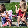 JAY YOUNG | THE GOSHEN NEWS<br /> Dressed in a red, white and blue dress, three-year-old Rosalie Meister, left, leans in as she watches the Northridge High School marching band approach while her sister, Ruby, 5, both of Middlebury, waves to the band during a Memorial Day parade in downtown Middlebury Monday morning.