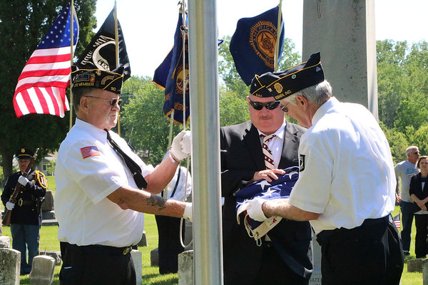 SHEILA SELMAN | THE GOSHEN NEWS<br /> Veterans raise the flag at Oakridge Cemetery in Goshen Monday for Memorial Day services. The three men raising the flag are, from left, Mike Wheeler, representing the Disabled American Veterans; Randy Troyer, DAV commander; and Terry Morgan, American Legion commander.