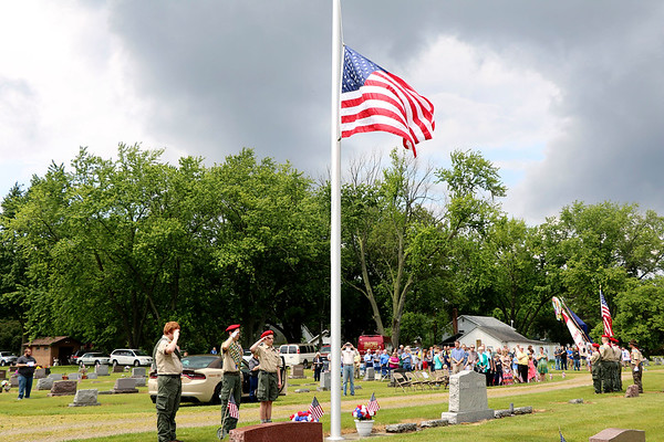 SHERRY VAN ARSDALL | THE GOSHEN NEWS<br /> New Paris Boy Scouts Troop 12 raised the flag during the Memorial Day services in New Paris Cemetery in New Paris Sunday. A brief thunderstorm delayed the services by 15 minutes.