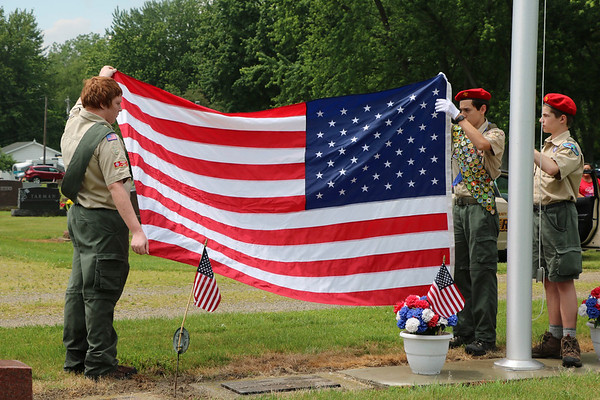 SHERRY VAN ARSDALL | THE GOSHEN NEWS<br /> From left, Ian Hansel, Nathan Hite and Philip Culp, members of New Paris Boy Scouts Troop 12, raised the flag during the Memorial Day services in New Paris Cemetery in New Paris Sunday. A brief thunderstorm delayed the services by 15 minutes.