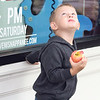 JULIE CROTHERS BEER | THE GOSHEN NEWS<br /> Remington Barth, 3, of Ligonier snacks on an apple while waiting with his mom Jessica Barth for the parade to begin Saturday during the Nappanee Apple Festival.