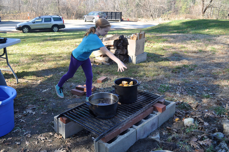Grace Merselis, 8, of Williamstown, throws apples into a heated pot in order to make apple sauce at Pine Cobble's family food day Saturday.  Members of the community were invited to sample healthy food and to take part in activities. (Jack Guerino/North Adams Transcript)