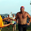 SHERRY VAN ARSDALL | THE GOSHEN NEWS<br /> Particpants accepted glasses of water from Donna Patuzzi, Twyla Kendrick and Jen Bowman at the first transition area during the Rock the Quarry Triathlon at Fidler Pond in Goshen Saturday.