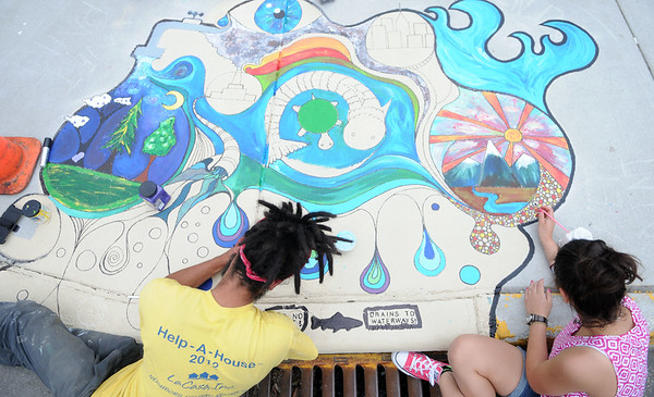 Haley Ward | The Goshen News<br /> Jairo Jimenez and Salome de Moya, 12, paint a storm drain for the Storm Drain Art project on Thursday at the corner of Fifth and Jefferson Streets. The project features eight murals created by 10 artists throughout Goshen. Jimenez said he's an abstract artist. He wanted to show the cycle of water, starting with the facet and showing it through different cycles with the river and even pollution. View more Storm Drain Art project photos at goshennews.com.