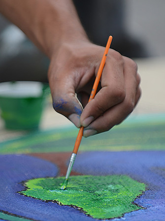 HALEY WARD | THE GOSHEN NEWS<br /> Jairo Jimenez fillls in trees with paint for the Storm Drain Art Project on Thursday at the corner of Fifth and Jefferson Streets. Jimenez is one of 10 artists working on eight different murals throughout Goshen.