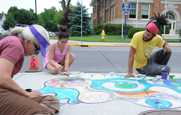HALEY WARD | THE GOSHEN NEWS<br /> Susana Cabezas, Salome de Moya and Jairo Jimenez paint a storm drain for the Storm Drain Art Project on Thursday at the corner of Fifth and Jefferson Streets. The storm drain water in Goshen leads to the Elkhart River or Rock Run Creek and what is in the roadways can pollute the water.