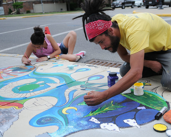 HALEY WARD | THE GOSHEN NEWS<br /> Salome de Moya, 12, and Jairo Jimenez paint a storm drain for the Storm Drain Art Project on Thursday at the corner of Fifth and Jefferson Streets. Jimenez, the artist on this particular drain, said he mostly wanted to do the line work and involve the community in filling in the color like de Moya who stopped by and volunteered.