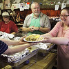 GEOFF LESAR | THE GOSHEN NEWS<br /> <br /> Josh Carpenter, left, of Goshen, passes a plate of food to Jennie Hile, right, owner of The Pizza Depot in Millersburg, Wednesday afternoon during the restaurant's sixth annual free Thanksgiving Day meal, as Marion Carpenter, center right, of Pierceton,  and  Deb Carpenter, of Pierceton, look on.