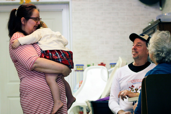 GEOFF LESAR | THE GOSHEN NEWS<br /> <br /> The Pizza Depot owner Jennie Hile, left, holds her daughter, Grace, as she talks to Gary Kauffman of Millersburg during the restaurant's sixth annual free Thanksgiving Day meal Wednesday in Millersburg.
