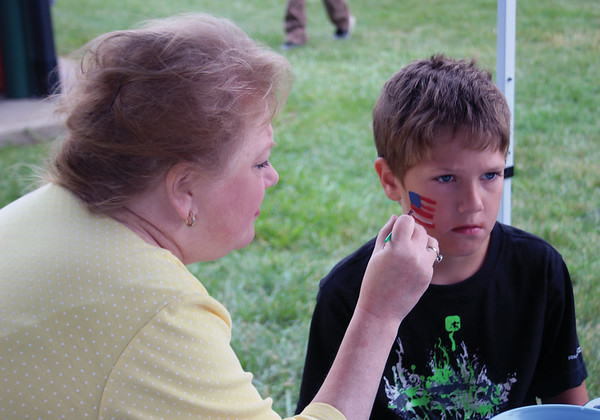 JOHN KLINE | THE GOSHEN NEWS<br /> Ryan Bailey, 7, of Elkhart, tries his best not to move as Goshen resident Lori Wilson paints an American flag on his cheek during Fourth of July festivities in Topeka Monday afternoon.