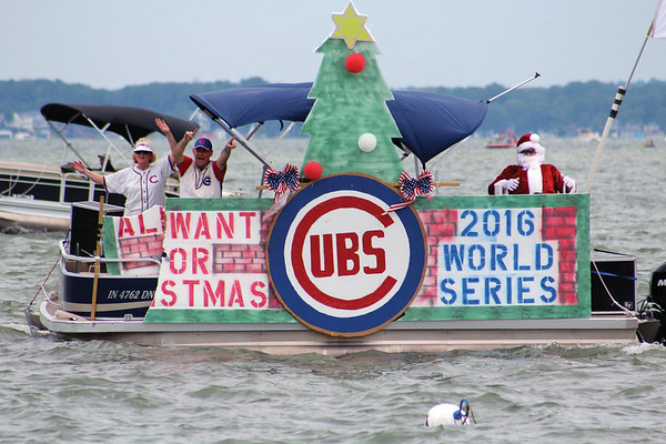 "JULIE CROTHERS BEER | THE GOSHEN NEWS<br /> Cubs fans wave from their boat as they pass Oakwood Resort in Syracuse during the 55th Wawasee Flotilla parade Sunday afternoon. This year's theme was ""Christmas in July."""