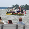 "JULIE CROTHERS BEER | THE GOSHEN NEWS<br /> A group of spectators watch as the Noel Belle passes the dock at Oakwood Resort in Syracuse during the 55th Wawasee Flotilla parade Sunday afternoon. This year's theme was ""Christmas in July."""