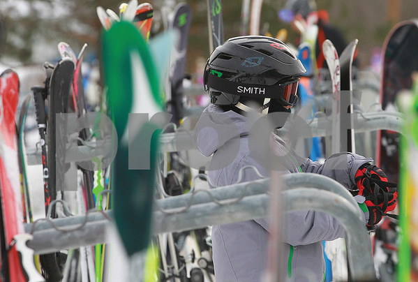 Spencer Tulis/Finger Lakes Times With winter recess in progress, cold temperatures a some snow on the ground, Bristol Mountain was a great place to be Saturday. Neil Stringer, 11, of Canandaigua gets gathers his skis from a rack as he prepares to hit the slopes with his parents.