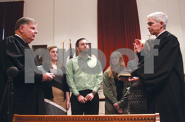 Spencer Tulis/Finger Lakes Times Former Wayne County District Attorney Rick Healy (right) was sworn in by retiring Judge Dennis Kehoe Friday at a ceremony at the historic courthouse in Lyons Friday. Looking on are (l-r) Step children Nick and MaKenzie Botcher, daughter Emma and wife Lori.