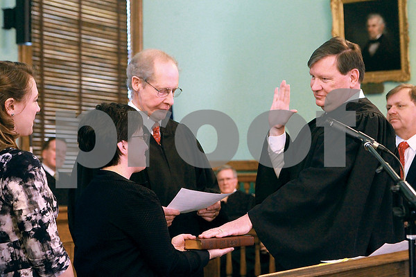 Spencer Tulis/Finger Lakes TimesNew Ontario County Judge Brian Dennis was sworn in Wednesday during a ceremony at the county courthouse in Canandaigua. He took the oath of office from retired county Judge Jim Harvey while Dennis' wife, Anna Polimeni, held the Bible and family members looked on.