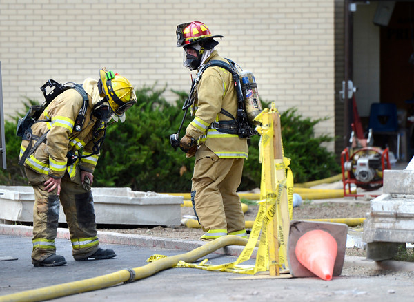 "A firefighter, at left, catches his breath before going back into the scene where an alleged roof collapse had trapped people inside on Wednesday, Aug. 1, at Erie Middle School in Erie. For more photos and video of the accident go to  <a href=""http://www.dailycamera.com"">http://www.dailycamera.com</a><br /> Jeremy Papasso/ Camera"