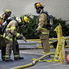 A rescue worker is helped with his oxygen before going into the Erie middle school building after the an explosion Wednesday afternoon. August 1, 2012. Rachel Woolf/ For the Daily Camera