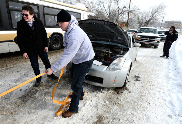 Corey Hyatt gets a tow cable set up to help Alex Schafer, left, to get his car unstuck on a hill on Colorado Avenue outside the University of Colorado on a snowy Thursday morning in Boulder.<br /> February 21, 2013<br /> Photo by Paul Aiken