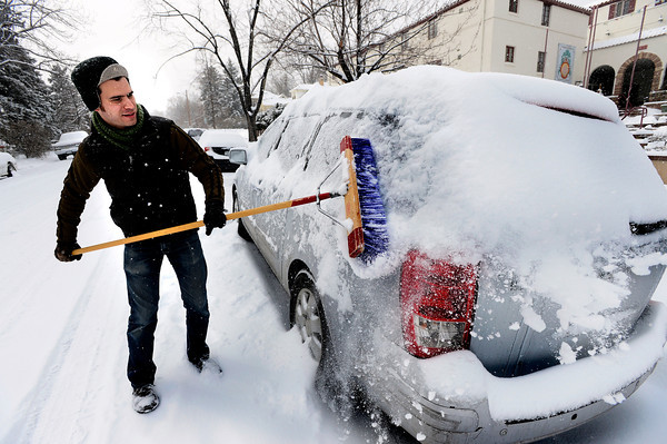Ian McLaughlin cleans off a car outside Marpa House where he works on a snowy Thursday morning in Boulder.<br /> February 21, 2013<br /> Photo by Paul Aiken