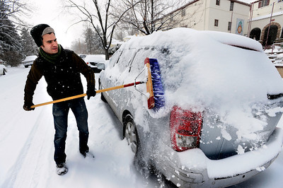 Ian McLaughlin cleans off a car outside Marpa House where he works on a snowy Thursday morning in Boulder. February 21, 2013 Photo by Paul Aiken