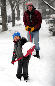 COBOU101.JPG Levi Mushovic, 4, helps his dad Brad clean their neighborhood sidewalk in Boulder, Colo on a snowy Thursday morning. Thursday February 21, 2013 Photo by Paul Aiken / The Daily Camera /