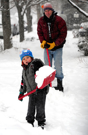 COBOU101.JPG Levi Mushovic, 4, helps his dad Brad clean their neighborhood sidewalk in Boulder, Colo on a snowy Thursday morning.<br /> Thursday February 21, 2013<br /> Photo by Paul Aiken / The Daily Camera /