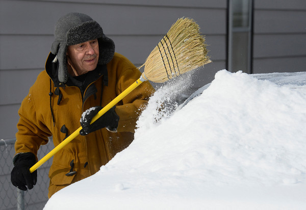20130221_WEATHER_.jpg William Martinez clears snow from his car in front of his home on Terry Street, near 11th Avenue, Thursday morning Feb. 21, 2013. Martinez said he was going out for a cup of coffee. (Lewis Geyer/Times-Call)