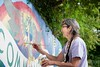 KELLY FLETCHER, REFORMER CORRESPONDENT -- Kate Richardson paints a phoenix on the neighborhood mural, the theme of which is gratitude, during the FEET block party at Lynch Park on Elliot Street on Sunday