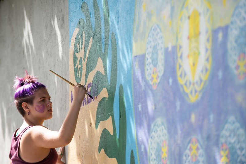 KELLY FLETCHER, REFORMER CORRESPONDENT -- Chloe Bell paints a memorial for Andrew Hale on the mural on Elliot Street which was created by the community during the FEET (Frost, Elm, Elliot triangle)  block party on Sunday