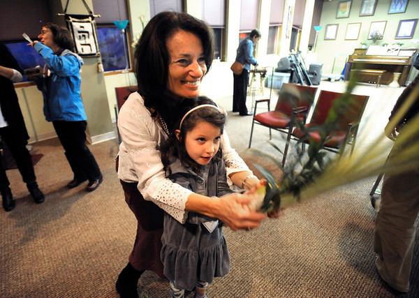 "Rabbi Tirzah Firestone helps Cora Brockman Hicks, 6, wave the Four Species including the lulav and etrog to the four compass points and upwards and downwards as part of the Festival of Sukkot at the Jewish Renewal Community of Boulder - Nevei Kodesh on Wednesday evening. Historically, Sukkot commemorates the forty-year period during which the children of Israel were wandering in the desert, living in temporary shelters. FOR MORE PHOTOS FROM THE FESTIVAL GO TO  <a href=""http://WWW.DAILYCAMERA.COM...Photo"">http://WWW.DAILYCAMERA.COM...Photo</a> by Paul Aiken / October 12, 2001..."