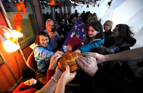 "The Challah bread is broken as part the Festival of Sukkot at the Jewish Renewal Community of Boulder - Nevei Kodesh on Wednesday evening. From left to right Dena Gitterman, Francesca Metzger, 8  and Hana Flinkman, 10, sit inside the Sukkah or temporary dwelling that is built as part of the festival and decorated with things grown from the ground like flowers, branches and fall garden vegetables like squash. Historically, Sukkot commemorates the forty-year period during which the children of Israel were wandering in the desert, living in temporary shelters. FOR MORE PHOTOS FROM THE FESTIVAL GO TO  <a href=""http://WWW.DAILYCAMERA.COM...Photo"">http://WWW.DAILYCAMERA.COM...Photo</a> by Paul Aiken / October 12, 2001..."