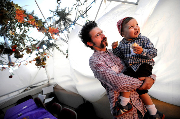 Jason Hicks with his son Ezra Brockman Hicks, 2, look over the Sukkah or temporary dwelling that is built as part of the festival Festival of Sukkot at the Jewish Renewal Community of Boulder - Nevei Kodesh on Wednesday evening. The Sukkah is traditionally decorated things ground from the ground including flowers, branches and fall garden vegetables like squash. Historically, Sukkot commemorates the forty-year period during which the children of Israel were wandering in the desert, living in temporary shelters. <br /> Photo by Paul Aiken / October 12, 2001