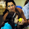 "Tara Brockman Hicks helps her daughter Cora, 6, smell the etrog, a citrus fruit native to Israel, as part of the Festival of Sukkot at the Jewish Renewal Community of Boulder - Nevei Kodesh on Wednesday evening. The etrog is used as part of a traditional blessing. Historically, Sukkot commemorates the forty-year period during which the children of Israel were wandering in the desert, living in temporary shelters. FOR MORE PHOTOS FROM THE FESTIVAL GO TO  <a href=""http://WWW.DAILYCAMERA.COM...Photo"">http://WWW.DAILYCAMERA.COM...Photo</a> by Paul Aiken / October 12, 2001..."