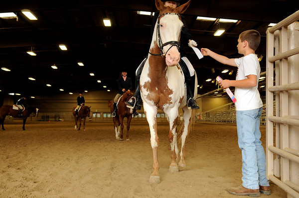 Sam Barnes, 10, of Mead, at right, hands a fourth-place ribbon to Jessica Koral, 13, of Boulder, after she competed in the English Control event at the Indoor Arena at the Boulder County Fairground in Longmont on Thursday, July 29.<br /> Jeremy Papasso/ Camera