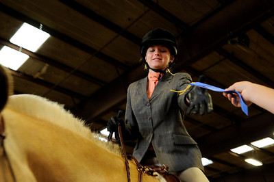 Katlyn Biesiada accepts her first-place ribbon from Sam Barnes, at right, after winning the Level I English Control event at the Indoor Arena at the Boulder County Fairground in Longmont on Thursday, July 29. Jeremy Papasso/ Camera