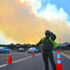 12EPNews Fire from Gate.jpg Ranger Kelly Azatt keeps a lane open for emergency vehicles at the Beaver Meadows entrance station on Tuesday. The fire above Fern Lake grew to over 300 acres over the afternoon and and evening.