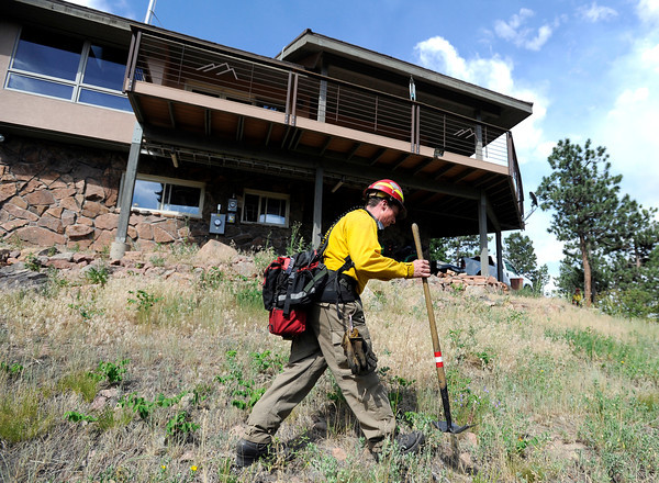 "Rocky Mountain Fires Aaron Peavey walks the perimeter of a home that was evacuated while fighting the Flagstaff wildfire on Tuesday, June 26, in Boulder. For a video of the fire go to  <a href=""http://www.dailycamera.com"">http://www.dailycamera.com</a><br /> Jeremy Papasso/ Camera"