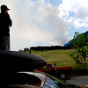 Eric Sutter, of Boulder, looks up at the fire burning from the top of his car at the bottom of Baseline Rd. Tuesday afternoon. Rachel Woolf/ Daily Camera