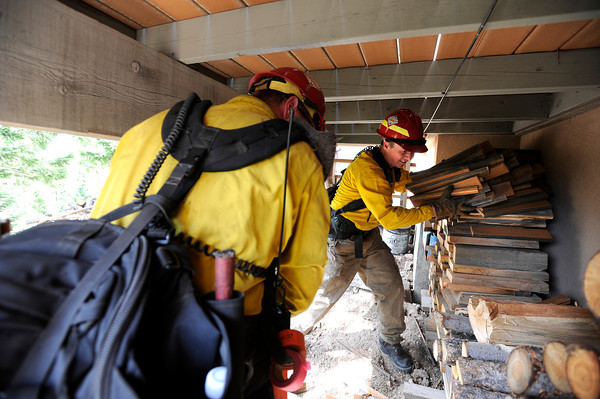 "Rocky Mountain Rescue workers Aaron Peavey, right, and Kyle Lyman work to remove a stack of wood from under a porch of a home while fighting the Flagstaff wildfire on Tuesday, June 26, in Boulder. For a video of the fire go to  <a href=""http://www.dailycamera.com"">http://www.dailycamera.com</a><br /> Jeremy Papasso/ Camera"