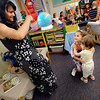 Claudia Borlovan takes a photo as her daughter Daniella at left hugs her younger sister Sonya, 2,  goodbye on the first day Daniella's kindergarten  at Ryan Elementary School in Lafayette on Monday Morning<br /> Photo by Paul Aiken / The Camera / 8/ 15/ 11