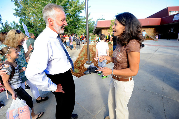 Kirsten Mays jokes with Boulder Valley School Superintendent Bruce Messinger as he visits Ryan Elementary in Lafayette on the first day of school on Monday morning.  Mays says she didn't recognize him as a parent riding on the bus with the student and wondered who he was. <br /> Photo by Paul Aiken / The Camera / 8/ 15/ 11