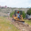 A mini-bulldozer preparing a back-burn fire break on the social trail behind View Point Road houses that border the open space. <br /> Photo Courtesy Thomas Duncan