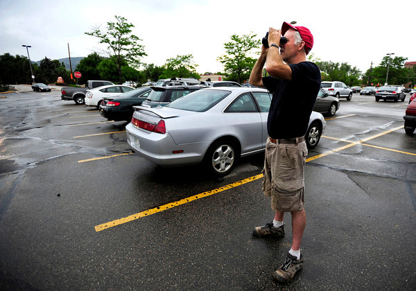 Brad D. Segal, of Boulder looks through binoculars at the Flagstaff Fire from the Basemar Shopping Center off of Baseline and Broadway. Segal has received a pre-evacuation notice for his home near Table Mesa. Daily Camera/Rachel Woolf