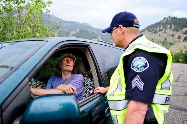 Officer Ed Quayle speaks to Dismas Rotta of Boulder at the road block off Baseline Road near where it turns into Flagstaff Road. Rotta was coming down the mountain after helping an individual with handywork beyond the roadblock. Daily Camera/ Rachel Woolf