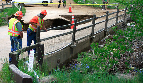 Bob Parrish and Chris Kelley of the Colorado Department of Transportation  look over the damaged bridge  in the Boulder Canyon Tuesday morning June 8,  above the city of Boulder, Colorado. Debris is backing water up behind the bridge. Authorities are worried about water releasing from the bridge and have closed most of the paths and bikeways along the creek in the city in case of a water surge.<br /> Photo by Greg Lindstrom / Daily Camera / Photo by Greg Lindstrom / Daily Camera /