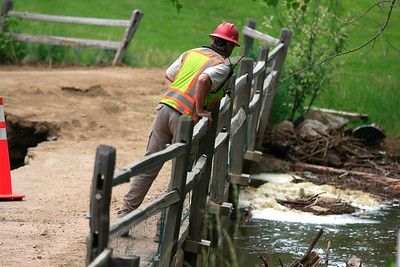 A worker looks into Boulder Creek near the collapsed area of the bridge in Boulder Canyon.  Photo by Greg Lindstrom / Daily Camera /