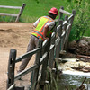 A worker looks into Boulder Creek near the collapsed area of the bridge in Boulder Canyon. <br /> Photo by Greg Lindstrom / Daily Camera /