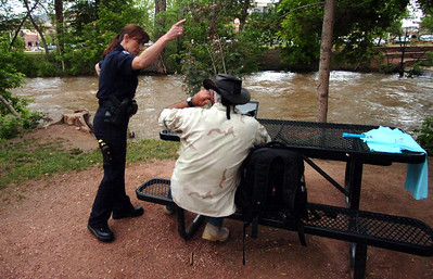 Boulder Police Officer S. Ramos moves Phil Callery from a bench next to Boulder Creek in Central Park  in Boulder on Tuesday morning June 8, 2010. The authorities were enforcing a closure of the creek path due to possible flooding. Photo by Paul Aiken / Daily Camera /