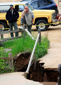 Chris Mueller, owner of the Red Lion Inn looks at the damaged bridge that separates his restaurant from Boulder Canyon Drive. Photo by Greg Lindstrom / Daily Camera /